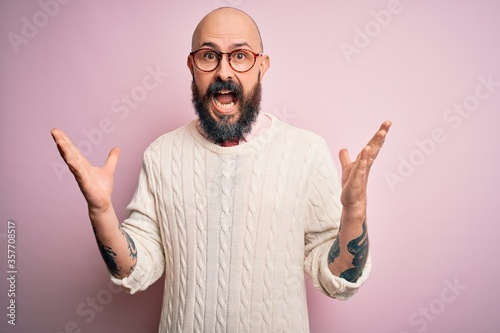 Handsome bald man with beard and tattoo wearing glasses and sweater over pink background celebrating crazy and amazed for success with arms raised and open eyes screaming excited Fototapeta