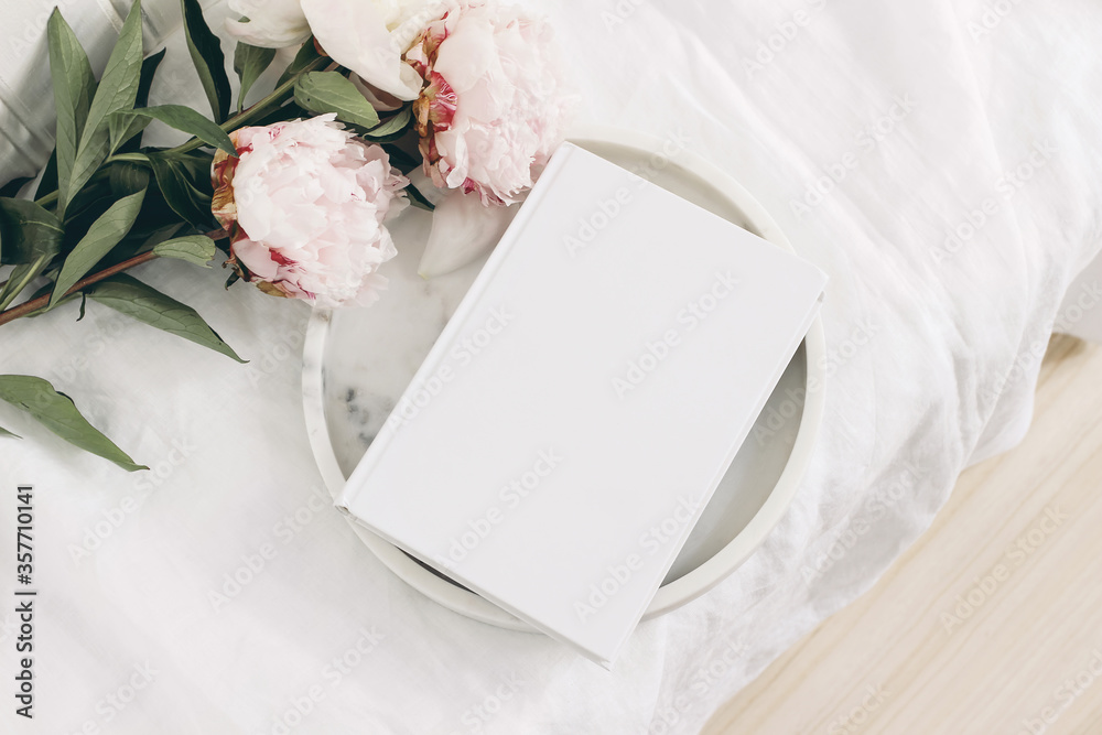Fototapeta Wedding still life scene. White empty book cover mockup on marble tray. Pink peony flowers on white linen table cloth. Vintage feminine styled photo, wooden floor. Flat lay. Blurred background.