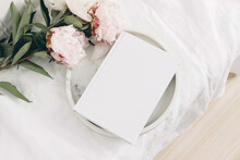 Wedding Still Life Scene. White Empty Book Cover Mockup On Marble Tray. Pink Peony Flowers On White Linen Table Cloth. Vintage Feminine Styled Photo, Wooden Floor. Flat Lay. Blurred Background.