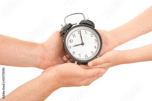 Hands of family with alarm clock on white background Wallpaper Mural
