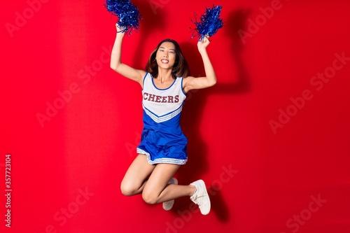Cuadros en Lienzo Young beautiful chinese girl smiling happy wearing cheerleader uniform