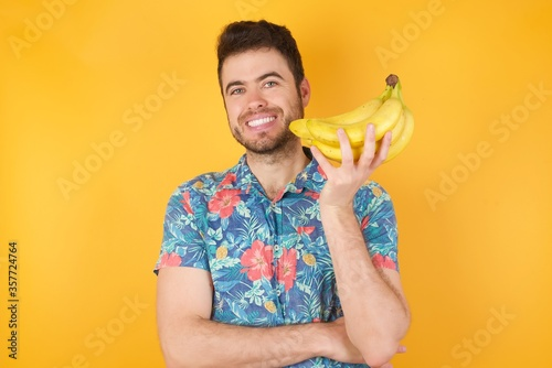 Foto Image of cheerful pretty young caucasian man standing against gray wall with hand near face