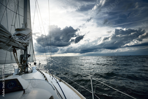 Fototapeta White yacht sailing in an open sea on a summer day