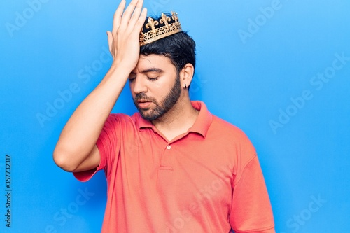 Foto Young hispanic man wearing king crown surprised with hand on head for mistake, remember error