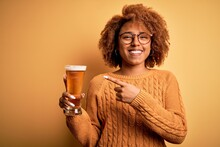 Young Beautiful African American Afro Woman With Curly Hair Drinking Glass Of Beer Very Happy Pointing With Hand And Finger