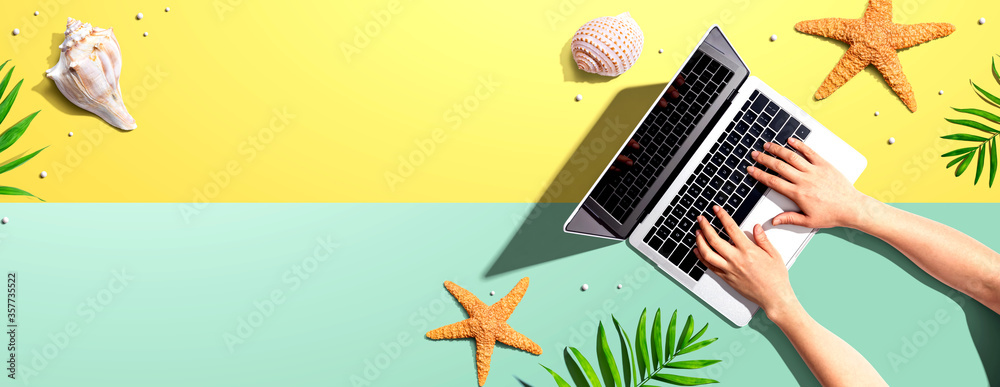 Fototapeta Person using a laptop computer with summer theme objects - flat lay