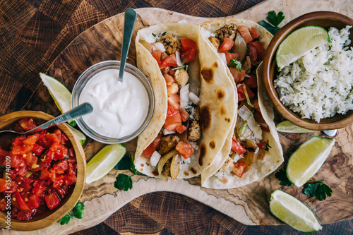 Fotomural An olive board filled with delicious Mexican fiesta of food tacos and burritos w