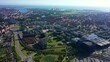 Aerial shot of cityscape by sea against sky on sunny day, drone flying forward over buildings in city - Copenhagen, Denmark