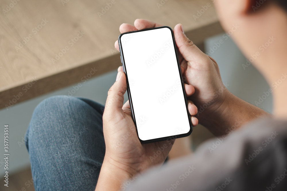 Fototapeta Top view Mockup image hand using a smartphone man Holding Cell Phone With Blank Screen