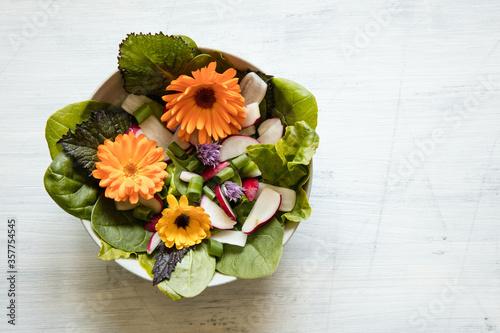 Schale mit Salat und essbaren Blüten auf hellem Holzuntergrund #357754545