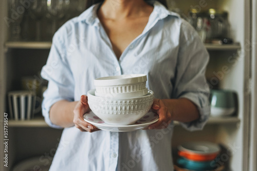 Fotografie, Tablou Crop photo of young woman in casual shirt with dishes near vintage sideboard at
