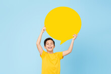 Waist Up Portrait Of Smiling Cute Asian Boy Holding Up An Empty Speech Bubble In Light Blue Studio Background