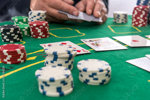 Photographie Male hand hold  chips and cards for poker on casino table