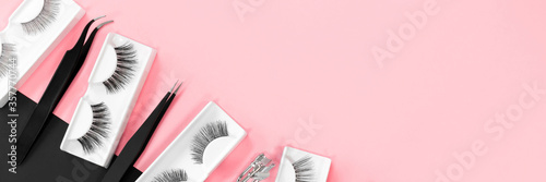 Fototapeta Various tools for eye lash extensions on a trendy pastel pink and black background