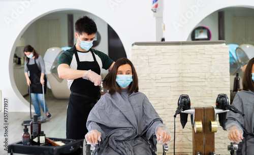 Man doing haircut for woman in salon using face masks