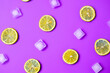 canvas print picture - Lemonade layout with juicy lemon slices, ice cubes on purple background