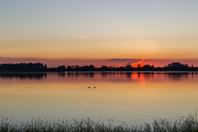 Ducks On The Water At Sunset O...