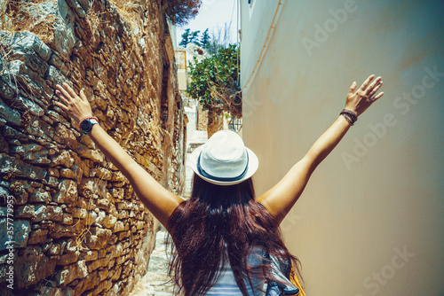 Foto Back side of young traveling woman walking and looking in Greek island of Symi, Dodecanese, Greece