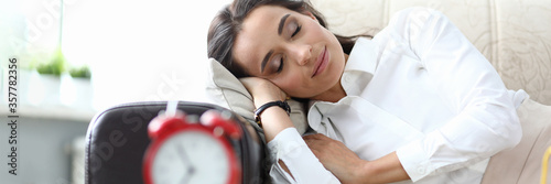 Fotomural Girl sleeps after work couch, table an alarm clock