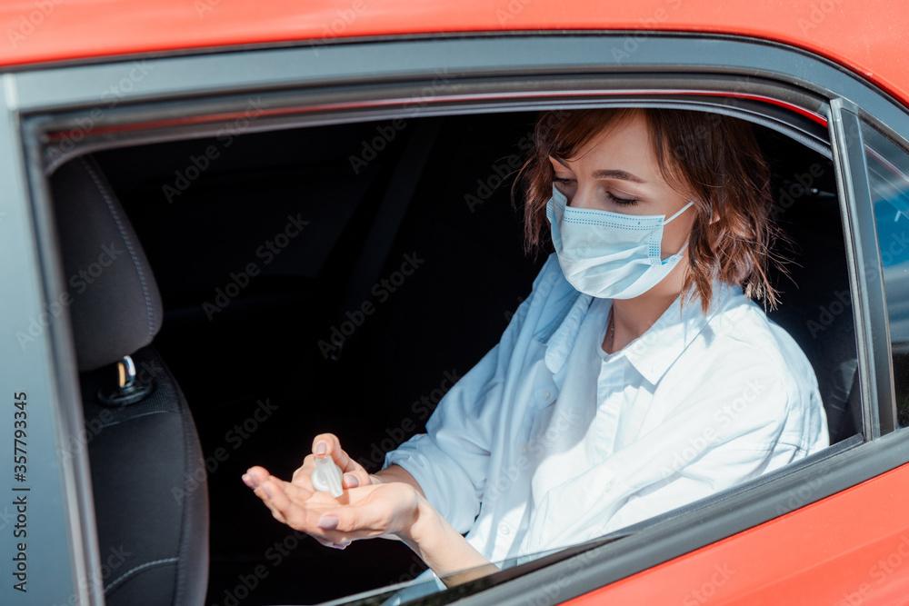 Fototapeta girl in medical mask using antiseptic in car during coronavirus pandemic