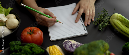 Fototapeta Female student taking recipe notes on blank notebook on black kitchen table in cooking class obraz