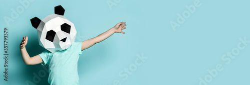 Baby boy kid in polygonal panda mask dancing with hands spread up popular sign on light blue фототапет