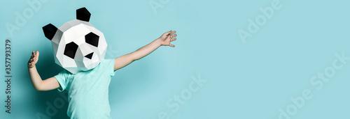 Fotografija Baby boy kid in polygonal panda mask dancing with hands spread up popular sign on light blue