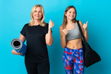 Mom And Daughter Doing Yoga Isolated On Blue Background Giving A Thumbs Up Gesture With Both Hands And Smiling