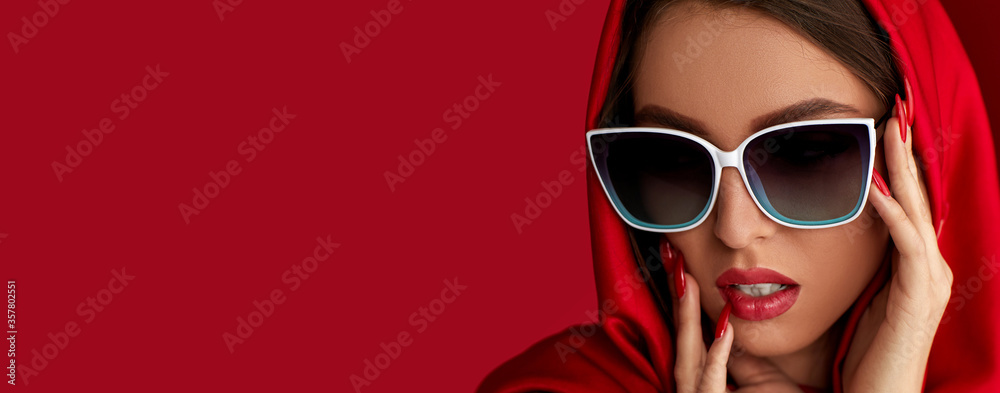 Fototapeta gorgeous brunette woman with luxurious make-up in white sunglasses and red headscarf on red background. copy space for text