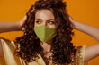 Fashionable curly woman wearing trendy outfit with green protective face mask. Summer fashion during quarantine of coronavirus outbreak. Model posing on orange background