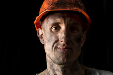 The Face Of A Male Miner In A Helmet On A Black Background.