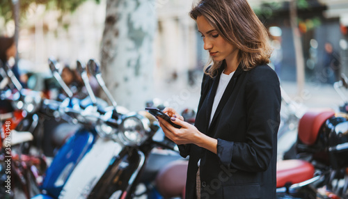Fototapeta elegant girl standing at parking mopeds on street city using  smart phone online app rents fast urban transport go work, woman in Barcelona looks at internet map in cellphone plans trip on scooter obraz