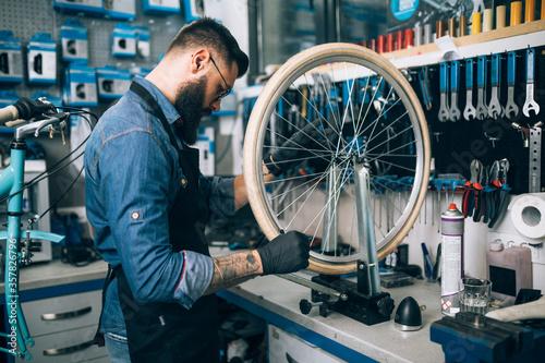 Young beard bicycle mechanic repairing bicycles in a workshop.. Fototapete