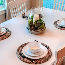 Square Dinner Table Setting With Tableware On Placemats Arranged Around A Centerpiece