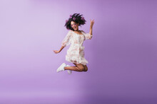 Portrait Of Funny African Girl In White Attire Jumping On Purple Background. Studio Shot Of Blithesome Brunette Young Woman Expressing Positive Emotions.