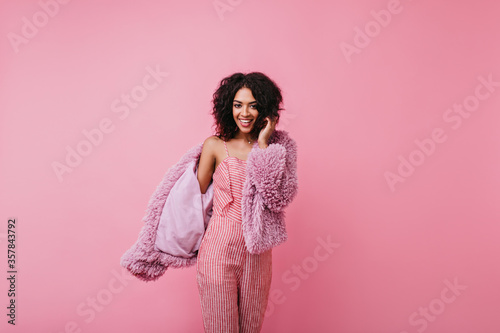 Vászonkép Cute curly girl with dark skin happily poses for her spring photo shoot