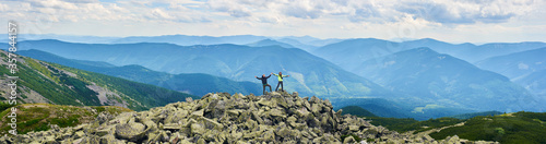 Fototapeta Panoramic view of loving couple holding hands up beautiful mountains scenery on background