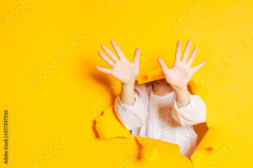 Fotografering Child hands is showing ten fingers through a ripped hole in yellow paper, with copy space