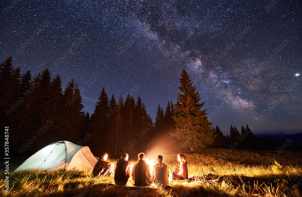 Fototapeta Night summer camping in the mountains, spruce forest on background, sky with stars and milky way. Back view group of five tourists having a rest together around campfire, enjoying fresh air near tent.