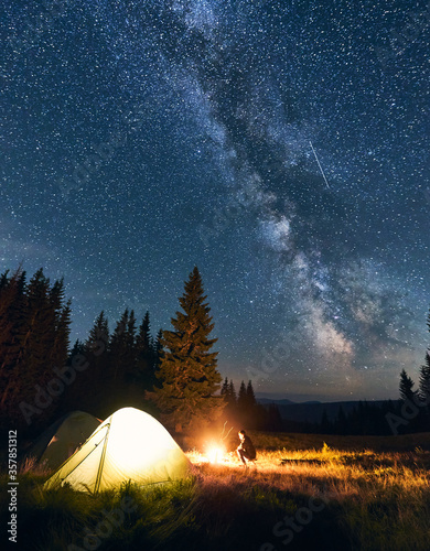 Fototapeta Lonely guy sitting near campfire in campsite under starry sky in the mountains. Night sky is strewn with bright stars and prominent Milky way. Tourist tents in valley with large pine trees. obraz na płótnie