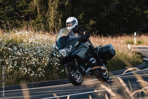 Motorradfahrer fährt mit seiner Tourenmaschine durch den Sonnenuntergang