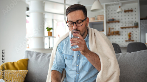 Sick man checking medicine package Tablou Canvas
