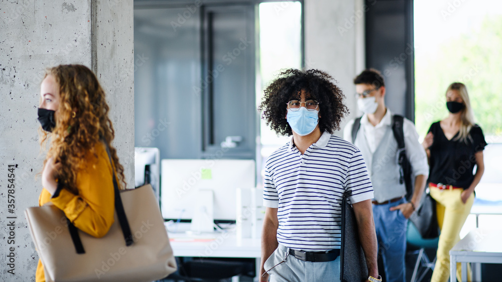 Fototapeta Young people with face masks back at work in office after lockdown, walking.