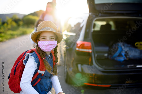 Small girl with family on trip outdoors in nature, wearing face masks Canvas Print