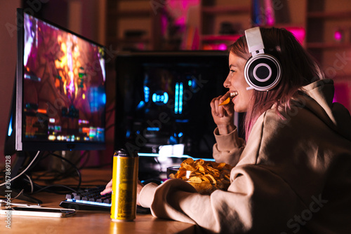 Canvastavla Image of delighted cute girl eating chips while playing video game