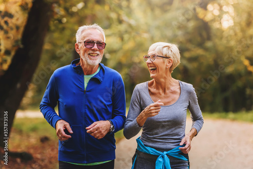 Fototapeta Smiling senior couple jogging in the park obraz