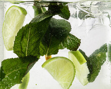 Close Up View Of The Cold And Fresh Lemonade With Lime Slices, Ice Cubes And Mint Leaves. Texture Of Cooling Summer's Drink With Macro Bubbles On Glass. Fizzing Or Floating Up To Top Of Surface.