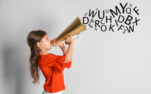 Adorable Little Girl With Vintage Megaphone And Letters On Light Background. Speech Therapy Concept