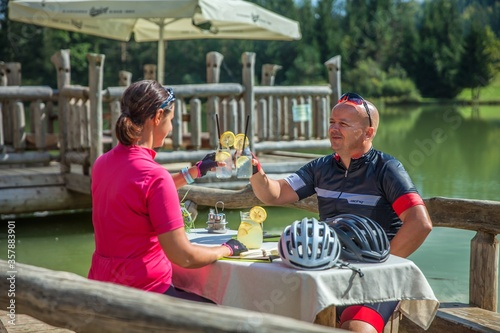 Fototapeta Biker couple having a break at Lake Bloke drinking lemonade after a bike tour