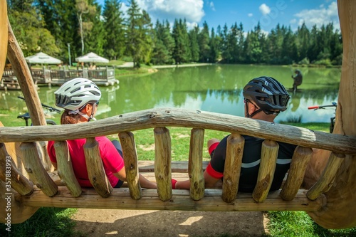 Biker couple on a tour at Lake Bloke resting on a wooden swing Canvas Print